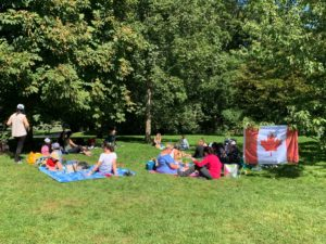 People sitting outside and Canada flag